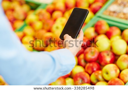 Male hand holding smartphone in front of fruits in a supermarket