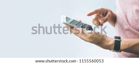 Male hand  holding smartphone,mobile with copy space on banner size  background.panoramic images