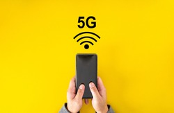 Male hand holding smartphone with 5G signal on yellow color background with copy space.