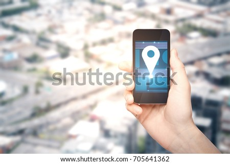 Male hand holding smartphone with location pin icon on blurry city background with copy space. Navigation concept  #705641362