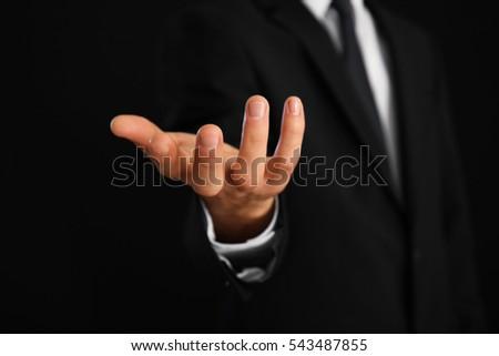 Male hand holding something on dark background #543487855