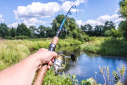Male hand holding spinning rod on the background of the river/Spinning fishing. Male hand holds spinning rod on the background of the river on a sunny day