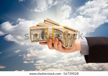 Male Hand Holding Stack of Cash Over Dramatic Clouds and Sky with Sun Rays.