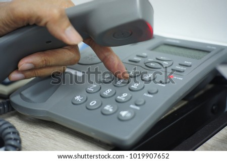 Male hand holding telephone and dailing a phone number.