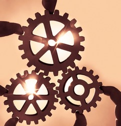 Male hand holding three wooden cog gear wheel on blue sunny sky background. sunshine and blue sky . sun rays.one part of whole. symbol of association and connection. business strategy
