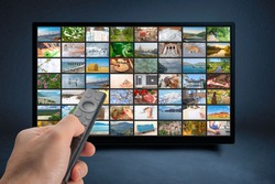 Male hand holding TV remote control. Multimedia streaming concept. VoD content provider concept. Television streaming video concept. Video service with internet streaming multimedia shows, series.