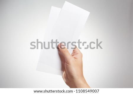 Male hand holding two blank sheets of paper (tickets, flyers, invitations, coupons, money, etc.), isolated on grey background