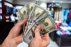 Male hand holding 100 us dollar money bills on mall store blurred background. customer concept