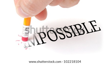 "Male hand holding wooden pencil and erase letters ""IM"" from word ""IMPOSSIBLE"""