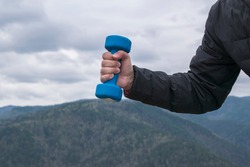 Male hand holds a blue dumbbell. Background sky, mountains. Bent at  elbow, hand and fingers tense. Concept of sports in nature.