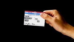Male hand holds a mock United State generic government Medicare Health Insurance card against black background