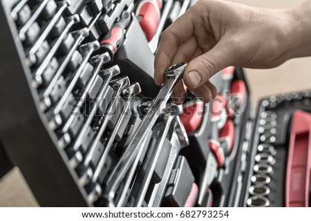 Male hand holds a spanner above the black toolbox. Inside it there are black-red pliers and screwdrivers, spanners and different nozzles. Closeup photo. Horizontal.