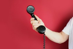 male hand holds a telephone receiver Handset from vintage apparatus on red background, concept of anonymous psychological assistance, helpline number, modern communication technology, call center