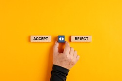 Male hand holds a wooden cube with arrow icon between the options of accept or reject. The decision or choice between accepting or rejecting.