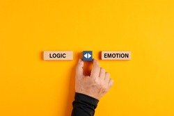 Male hand holds a wooden cube with arrow icon between the options of logic or emotion. Emotional or logical decision making concept.