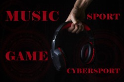 Male hand holds headphones on a black background. Computer technology concept. Cybersport.