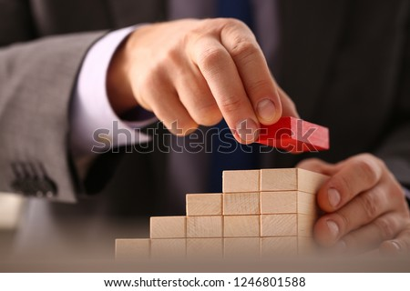 Male hand holds red wood block of stair finish next step rare progress personnel talent authority hot pyramid background on ladder different insurance concept closeup