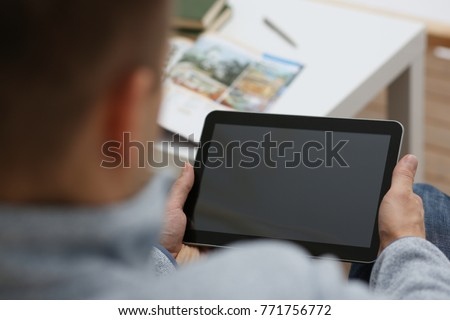 Male hand holds tablet pad in home setting while sitting on the couch engaged an internet surfing using application to press a finger on the display leisure listering music concept closeup. #771756772