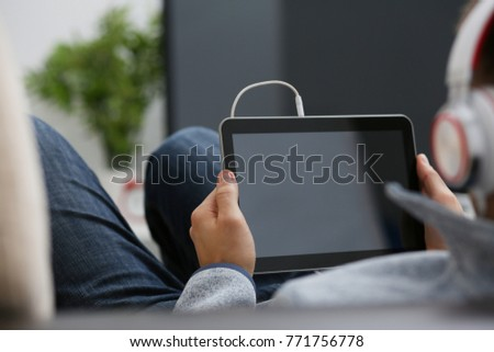 Male hand holds tablet pad in home setting while sitting on the couch engaged an internet surfing using application to press a finger on the display leisure listering music concept closeup. #771756778