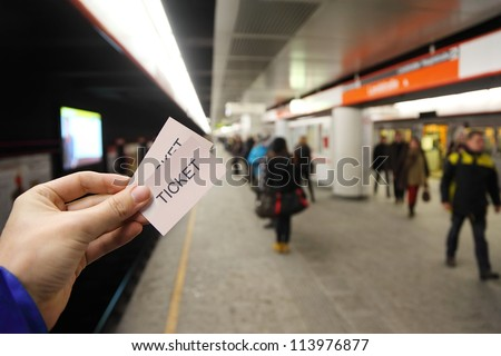 Male hand holds two tickets in subway. People wait for train on platform.
