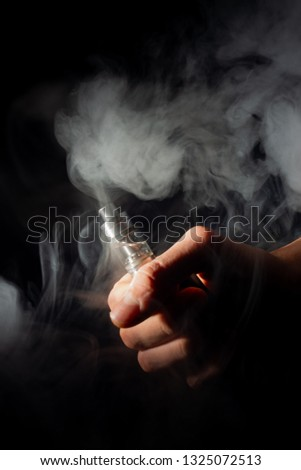 Male hand holds vape in thick vape fog or smoke. Vape clouds around hand with vape on black background. Fog is white. Stock isolated white smoke.