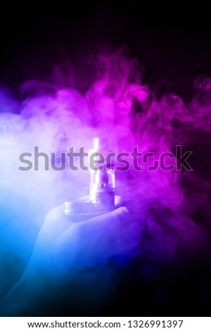 Male hand holds vape in thick vape fog or smoke. Vape clouds around hand with vape on black background. Fog is dual color — blue and purple. Stock isolated colorful smoke with spray glycerine.