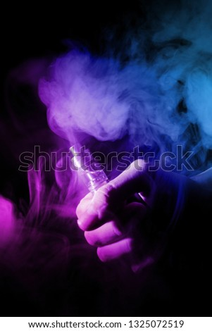 Male hand holds vape in thin vape fog or smoke. Vape clouds around hand with vape on black background. Light is dual color — blue and purple. Stock isolated colorful smoke with spray glycerine.