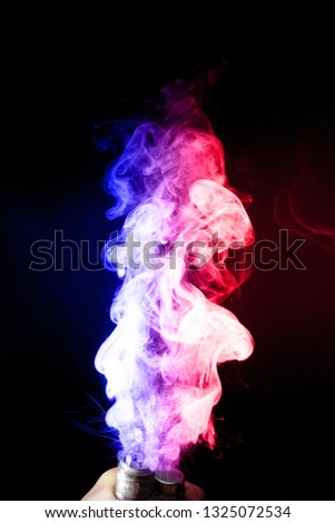 Male hand holds vape. Vape clouds splash from vape coil on black background. Fog is dual color — blue and red. Stock isolated dual colour smoke with spray boiling glycerine.