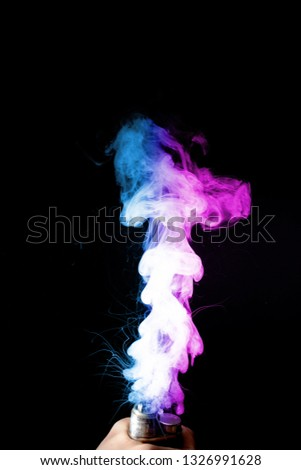 Male hand holds vape. Vape clouds splash from vape coil on black background. Fog is dual color — blue and purple. Stock isolated colorful smoke with spray boiling glycerine.