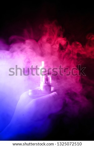 Male hand holds vape with atomiser in thick vape fog or smoke. Vape clouds around hand with vape on black background. Fog is dual color blue and red. Stock isolated colorful smoke with spray glycerine
