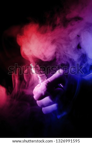 Male hand holds vape with atomiser in thick vape fog or smoke. Vape clouds around hand with vape on black background. Fog is dual color—blue and red. Stock isolated colorful smoke with spray glycerine