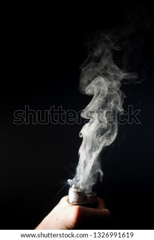 Male hand holds vape without atomiser. Column of vape clouds splash from coil on black background. Fog is white. Stock isolated white smoke with spray boiling glycerine.