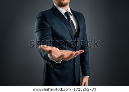 Male hand in a suit shows a palm up gesture on a gray background. Concept of request, bankruptcy, close-up Сток-фото ©