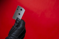 Male hand in black leather glove demonstrates three-piece of clubs on coral background. Right hand in black glove with single card. Divination or magician concept. Side view. Selective focus.