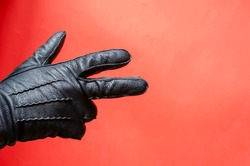 Male hand in leather glove gestures against coral background. Man shows his hand in black leather glove. Side view. Selective focus.
