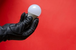 Male hand in leather glove holds light bulb. Right hand holding single white light bulb against coral background. Side view. Selective focus.