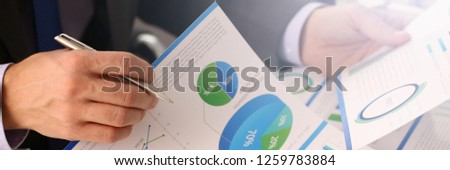 Male hand in suit hold siver pen in office with clipboard on table closeup. Comprehensive audit of enterprise business at all stages development.