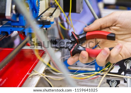 Male hand is configuring settings using nose pliers