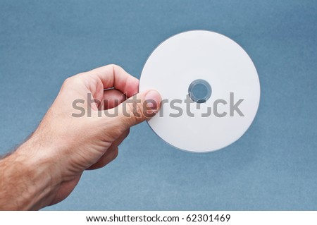 Male hand is holding a white CD.