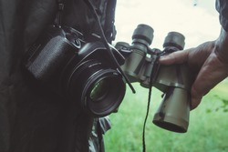 Male hand is holding binoculars on the background of nature; the camera is hanging near