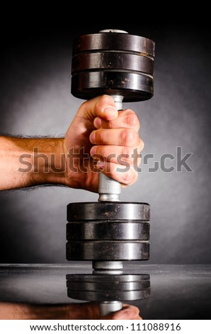 male hand is holding metal barbell on dark gray background