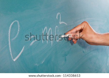 Male hand is writing Einstein's Formula E=mc2 on a blackboard