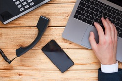 Male hand, laptop, IP phone, mobile phone and notebook on the wooden background. Top view. Ip telephony and video meetings for business concept.