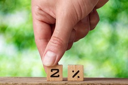 male hand lays out wooden cubes with percent on a green background. two percent on wooden cubes close up