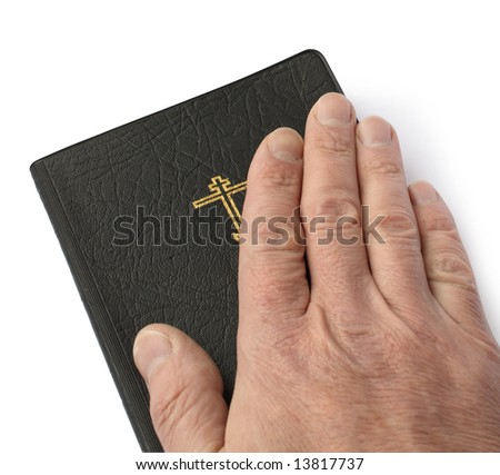 Male hand lying on black bible on white background