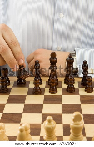 male hand moving chess black piece