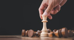 male hand moving chess piece on chess board game concept for ideas and competition and strategy, business success concept, business competition planing teamwork strategic concept.