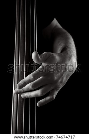 male hand on electric upright bass, toned monochrome image