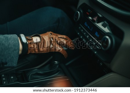 Male hand on gearstick of a manual car with brown leather driver gloves on and black smartwatch on right hand Stock photo ©