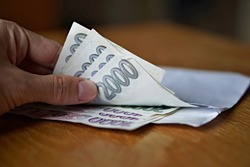 Male hand opening a white envelope full of Czech currency (Czech Crowns, CZK, Kc) on the wooden table as a symbol of cash transfer, money laundering or bribery